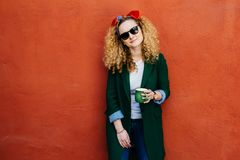 People and leisure concept. Horizontal portrait of pretty girl wearing headband, jacket, jeans and sunglasses holding cup of hot d stock image