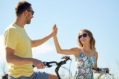 Happy couple with bicycles making high five Royalty Free Stock Images