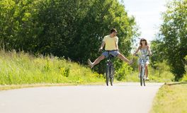 Happy young couple riding bicycles in summer. People, leisure and lifestyle concept - happy young couple riding bicycles along road in summer royalty free stock photography