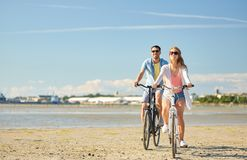 Happy young couple riding bicycles at seaside. People, leisure and lifestyle concept - happy young couple riding bicycles on beach stock photos