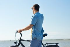 Man with bicycle on summer beach looking far away. People, leisure and lifestyle concept - happy young man with bicycle on summer beach looking far away royalty free stock image
