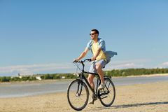Happy man riding bicycle along summer beach. People, leisure and lifestyle concept - happy young man riding bicycle along summer beach Royalty Free Stock Photo