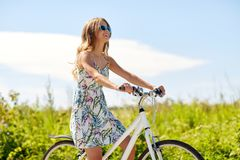 Happy smiling young woman riding bicycle in summer Stock Photo