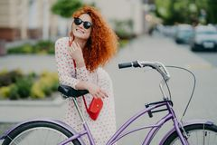 People, leisure, lifestyle and spare time concept. Cheerful curly woman focused into distance, rides bicycle in urban setting,. People, leisure, lifestyle and royalty free stock photo