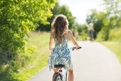 Woman riding bicycle at summer park. People, leisure and lifestyle - young woman riding bicycle at summer park royalty free stock photos