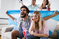 Happy and sad friends or football fans watching soccer game. People, leisure, rivalry and sport concept - happy and sad friends or football fans watching soccer Stock Image