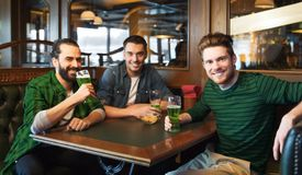 Male friends drinking green beer at bar or pub. People, leisure and st patricks day concept - happy male friends drinking green beer at bar or pub Royalty Free Stock Photography