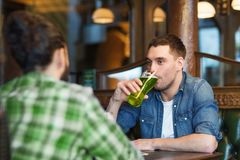 Male friends drinking green beer at bar or pub. People, leisure and st patricks day concept - happy male friends drinking green beer at bar or pub Royalty Free Stock Image