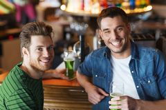 Male friends drinking green beer at bar or pub. People, leisure and st patricks day concept - happy male friends drinking green beer at bar or pub Stock Photo