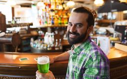 Man drinking green beer at bar or pub. People, leisure and st patricks day concept - happy man drinking green beer at bar or pub Royalty Free Stock Photos