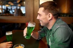Man drinking green beer at bar or pub. People, leisure and st patricks day concept - happy young man drinking green beer at bar or pub Stock Photo