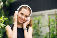 People leisure and technology concept - Attractive young woman listening to music on the music player in outdoors. Stock Images