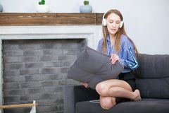 People, leisure and technology concept - happy woman or teenage girl in headphones listening to music from smartphone Royalty Free Stock Photography