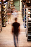 People in library aisle Stock Image