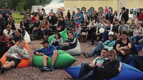 People lie on beanbags on ground in park. Summer festival. Love couple. Audience stock video