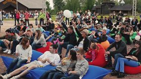People lie on huge beanbags in park. Summer festival. Wave balloons. Audience stock video footage
