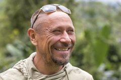 People and lifestyle concept. Happy middle-aged unshaven man with cheerful smile outdoor against green nature background, portrait Royalty Free Stock Photos