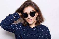People and lifestyle concept. Portrait of fashionable woman wearing round hipster sunglasses and stylish shirt looking at the came Stock Images