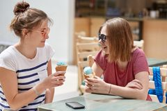 People, lifestyle and rest concept. Joyful hipsters have spare tine, eat delicious ice cream in cafe during summer, wear sunglasse stock photos