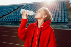 People, lifestyle and sport concept. Sport woman athlet overcame long distance, drinks water from plastic bottle, listens audio tr royalty free stock photo
