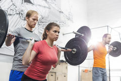 People lifting barbells in crossfit gym Stock Photo