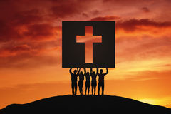 People lifting a crucifix symbol on the hill Royalty Free Stock Photos