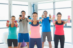 People lifting dumbbell weights with trainer in gym Royalty Free Stock Image
