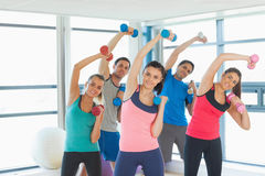 People lifting dumbbell weights with trainer in gym Stock Photography