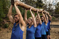 People lifting a heavy wooden log during boot camp Royalty Free Stock Photography