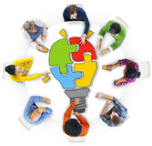 People with Light Bulb Jigsaw Puzzle Forming royalty free stock photography