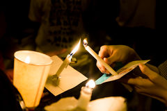 People lighting candle vigil in darkness seeking hope, worship, Stock Images