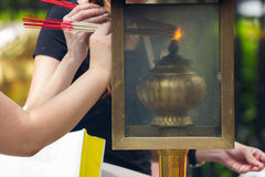 People lighting Incense sticks with lamp in Thailand Stock Photos