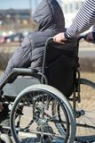 People with limited mobility take a walk by wheelchair. People with limited mobility take a walk by rollator wheelchair outdoors Royalty Free Stock Images