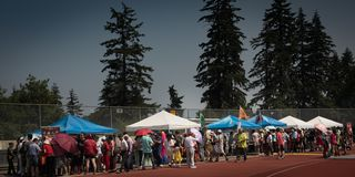 Its Chinese festival in Central Park Burnaby Canada. People line up for eating tradition food in festival market royalty free stock photography