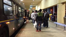 People line up for waiting bus stock video