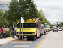 People lined up at food trucks at noon. Dallas, TX USA October 23, 2014: Office and park crowds line up at noon at the tree-lined food trucks parked in their Royalty Free Stock Image