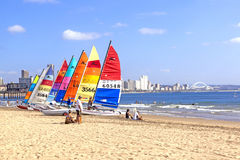 People and lined up sail boats against city skyline Royalty Free Stock Photos