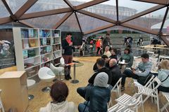People listen to a lecturer at Books of Russia. MOSCOW - JUNE 28, 2015: People listen to a lecturer at Books of Russia. Book fair on the Red Square in Moscow Royalty Free Stock Image
