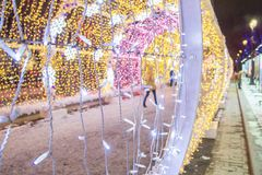People in lit with colored lights tunnel at Pushkinskaya square. Tverskaya street decorated for New Year and Christmas holidays royalty free stock photos