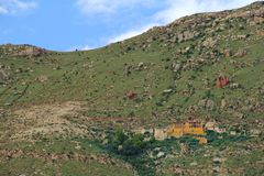 Rocks and green house located on streight green mountain. People live there in hill shows us strong mind against life time royalty free stock images