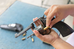 People load bullets into revolver gun Royalty Free Stock Photos