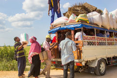 People loading cargo and luggage on local public transport vehicle. ZANZIBAR, TANZANIA - CIRCA JULY 2013: People loading cargo and luggage on local public Royalty Free Stock Photo