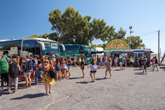 People and local buses on bus terminal in Thira town. Stock Photo