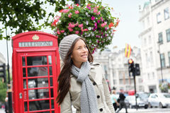People in London - woman by red phone booth. People in London- woman by red phone booth. Portrait of beautiful smiling happy young female casual professional Stock Images