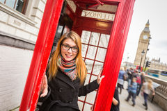 People in London. Young Woman next to London Traditional Telephone Booth Stock Photos