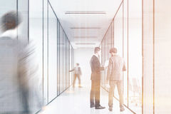 People in a long office corridor with glass walls. There are several conference rooms in it and. Royalty Free Stock Photography