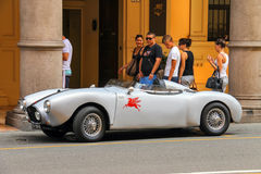 People look at an antique sports car parked in Bologna Royalty Free Stock Photos