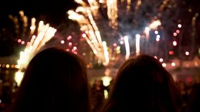 People look at the fireworks show on holiday in the evening at night stock footage