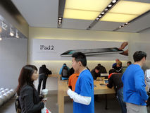 People look at products and talk to sales reps inside Apple Stor Royalty Free Stock Photo