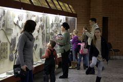 People look at the stand with fossils. Royalty Free Stock Image